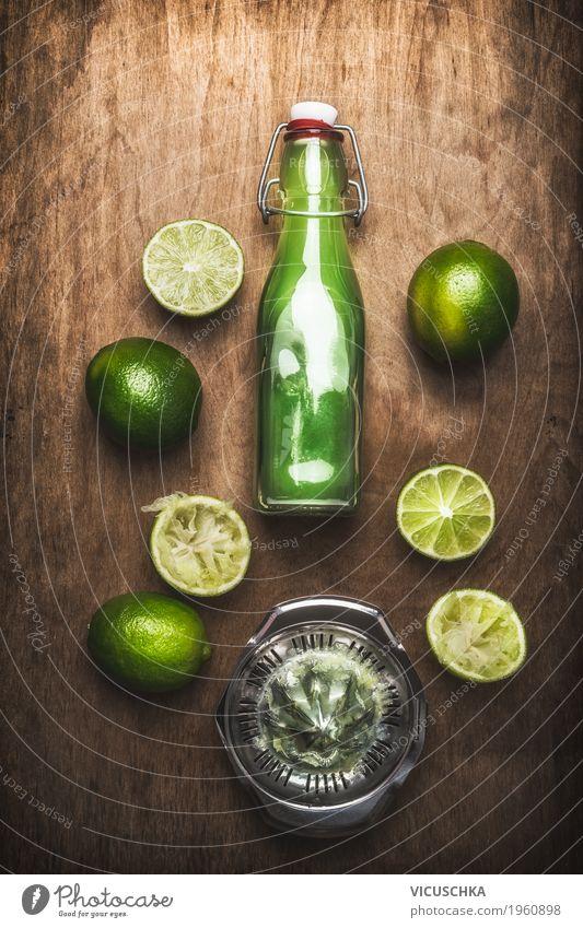 Limettensaft in Flasche mit Früchten und Saftpresse Sommer grün Gesunde Ernährung gelb Leben Stil Lebensmittel Design Frucht Tisch weich Getränk Küche