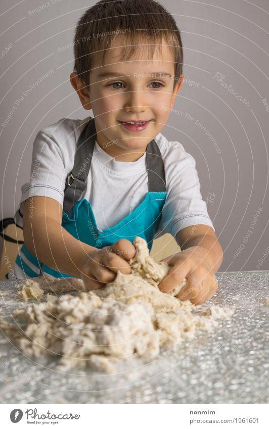 Kleiner Junge knetet rohen Pizzateig und -c $ lächeln Teigwaren Backwaren Brot Freude Spielen Küche Kind Lächeln machen blau reizvoll Schürze backen Bäcker