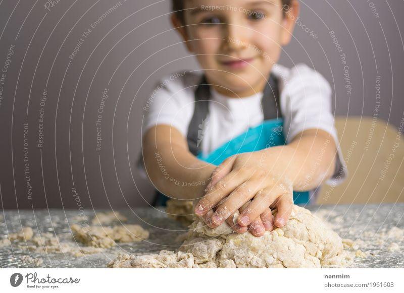 Kleiner Junge, der rohen Pizzateig knetet Kind blau Freude Spielen Lächeln Küche machen Brot reizvoll Backwaren Teigwaren Plätzchen Mehl