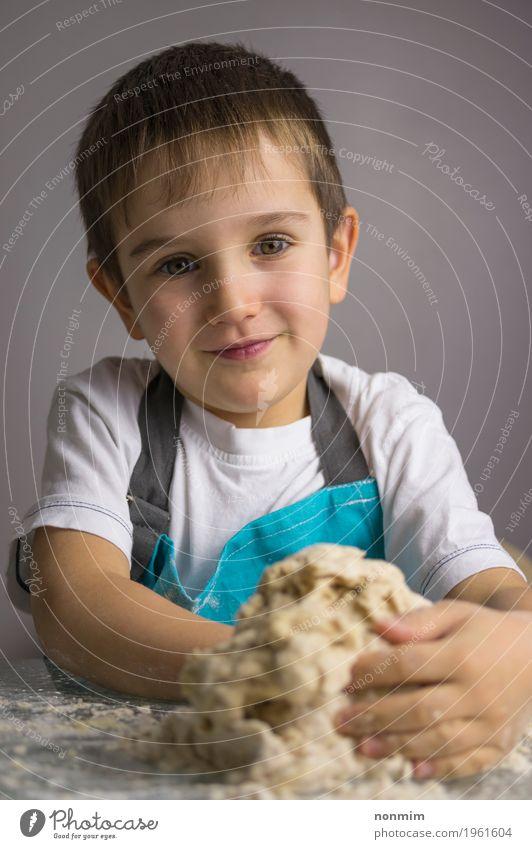 Kleiner Junge knetet rohen Pizzateig und -c $ lächeln Teigwaren Backwaren Brot Freude Küche Kind Kindheit Lächeln machen blau unschuldig reizvoll Schürze backen