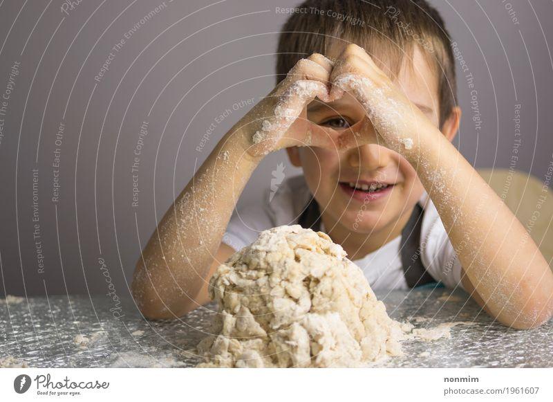 Junge knetet den rohen Teig, der durch Herzformhände schaut Kind Hand Freude Spielen Kindheit Lächeln Küche machen Brot reizvoll Backwaren Teigwaren Plätzchen