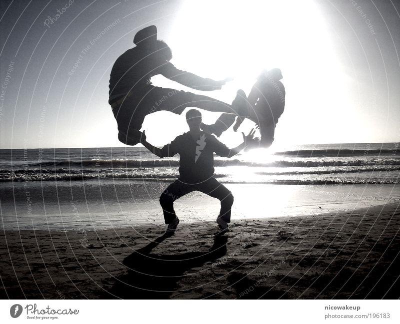 Kampfsport Mensch maskulin Junger Mann Jugendliche 18-30 Jahre Erwachsene Sonnenlicht Wellen Küste Strand Sand Wasser genießen springen Coolness lustig verrückt