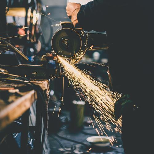 Metallschleifen auf Stahlersatzteil in der Werkstatt. Behandlung Arbeit & Erwerbstätigkeit Baustelle Fabrik Industrie Werkzeug Säge Maschine Baumaschine