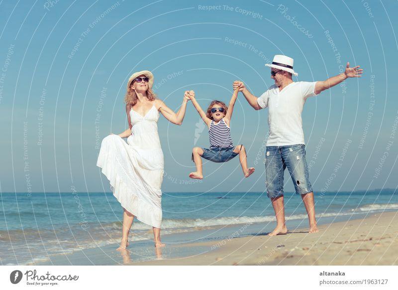 Glückliche Familie, die auf den Strand zur Tageszeit geht. Kind Frau Natur Ferien & Urlaub & Reisen Sommer Sonne Meer Erholung Freude Erwachsene Leben Liebe