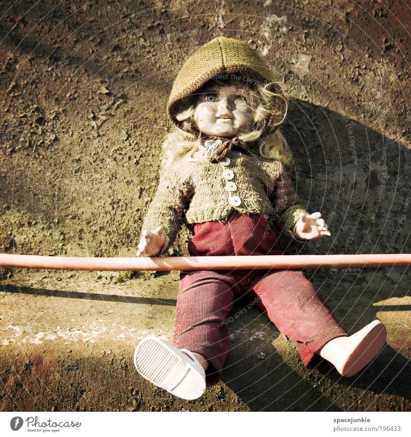 Die Puppe vom Schrottplatz Schuhe Mütze alt hässlich Einsamkeit Spielzeug sitzen skurril gruselig Kind Schlauch dreckig Mauer kahl Farbfoto Außenaufnahme