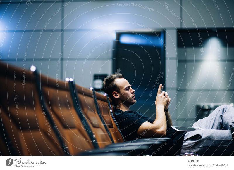 Junger erwachsener Mann, der in den Flughafenaufenthaltsraum unter Verwendung des intelligenten Telefons wartet Lifestyle Ferien & Urlaub & Reisen Ausflug Handy