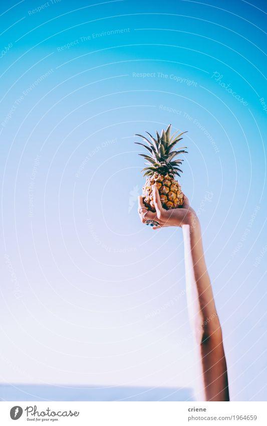 Nahaufnahme der Hand Ananas im blauen Himmel halten Lebensmittel Frucht Essen Lifestyle Freude schön Gesunde Ernährung Sommer Sommerurlaub Sonne Sonnenbad