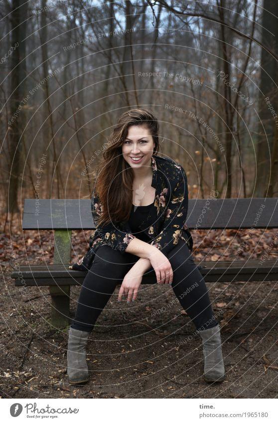 Anne feminin Frau Erwachsene 1 Mensch Wald Hose Jacke Stiefel brünett langhaarig Bank beobachten Lächeln lachen Blick sitzen warten Freundlichkeit Fröhlichkeit