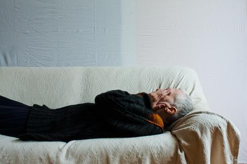 Mann liegt auf dem Rücken und auf einer Liege Bett liegen Sofa Mensch schlafen Mittagsschlaf ruhen Textfreiraum Polster Decke weiß Trauer Traurigkeit Kopf Hand