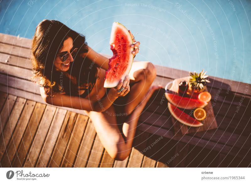 Junge schöne Frauen im Bikini, der am Swimmingpool sitzt Frucht Orange Essen Lifestyle Freude Schwimmbad Schwimmen & Baden Sommer Sommerurlaub Sonnenbad feminin