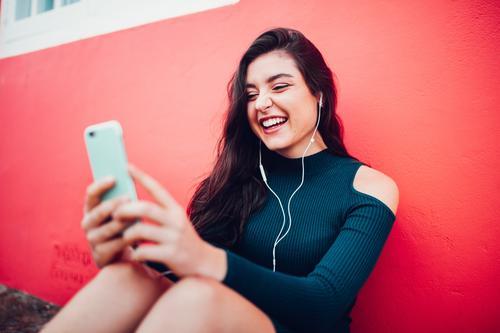 Glückliche kaukasische Frauen, die Musik am intelligenten Telefon hören Lifestyle Freude Handy MP3-Player PDA Technik & Technologie Unterhaltungselektronik