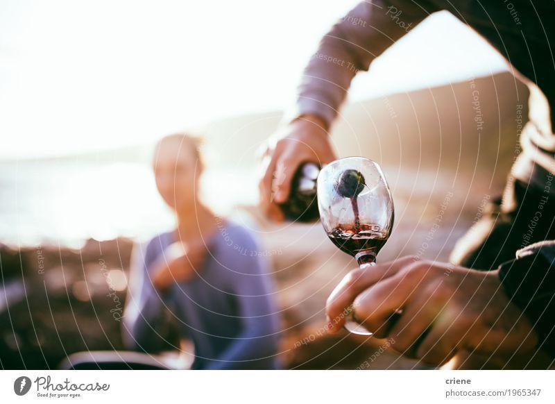 Füllendes Glas des Mannes mit Wein auf Datum am Strand im Sonnenuntergang Mensch Frau Jugendliche Sommer Freude Erwachsene Lifestyle Küste Glück Zusammensein
