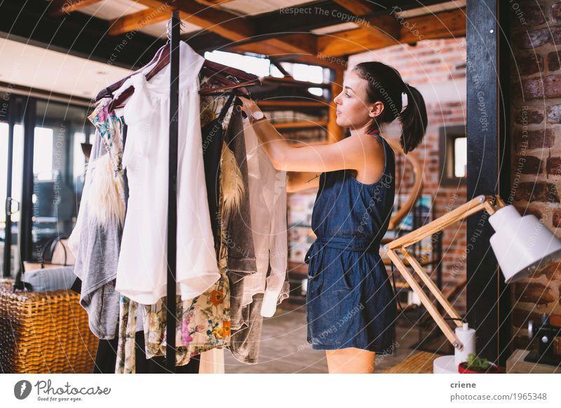Hängende Kleider des jungen weiblichen Designers auf Kleidungsschiene Mensch Jugendliche Junge Frau Freude 18-30 Jahre Erwachsene feminin Kunst Business Mode
