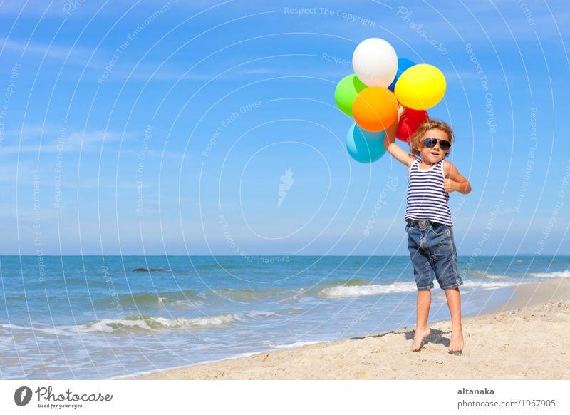 Kleiner Junge mit den Ballonen, die auf dem Strand stehen Lifestyle Freude Glück Erholung Freizeit & Hobby Spielen Ferien & Urlaub & Reisen Ausflug Abenteuer