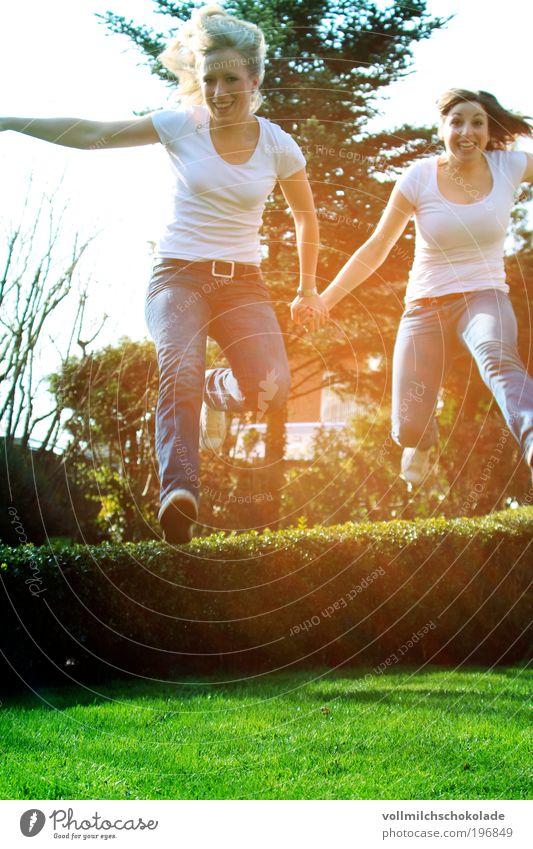 Ab durch die Hecke Mensch Natur Jugendliche feminin springen Frühling lachen Freundschaft Erwachsene laufen Umwelt Frau Gegenlicht Junge Frau Zeit Sonnenstrahlen