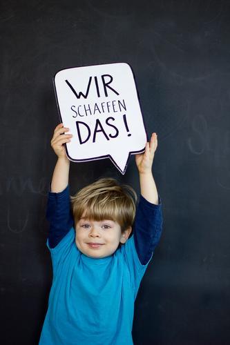 Wir schaffen das! Mensch Kind blau schwarz Gesicht Gefühle lustig Junge klein Schriftzeichen Kraft Kindheit Schilder & Markierungen Erfolg Lächeln niedlich