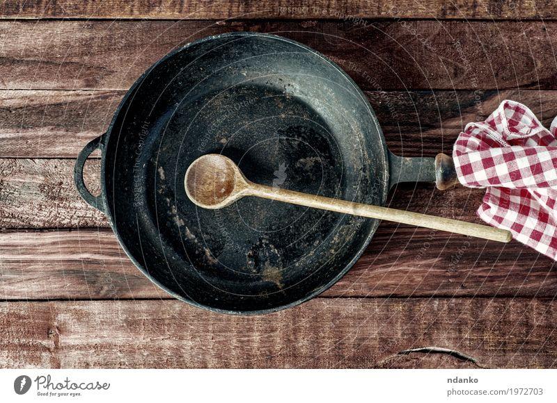 Schwarze Eisenpfanne mit einem Holzgriff und einem Löffel Geschirr Pfanne Tisch Küche Restaurant Stoff Metall Stahl oben Sauberkeit braun schwarz Tischwäsche