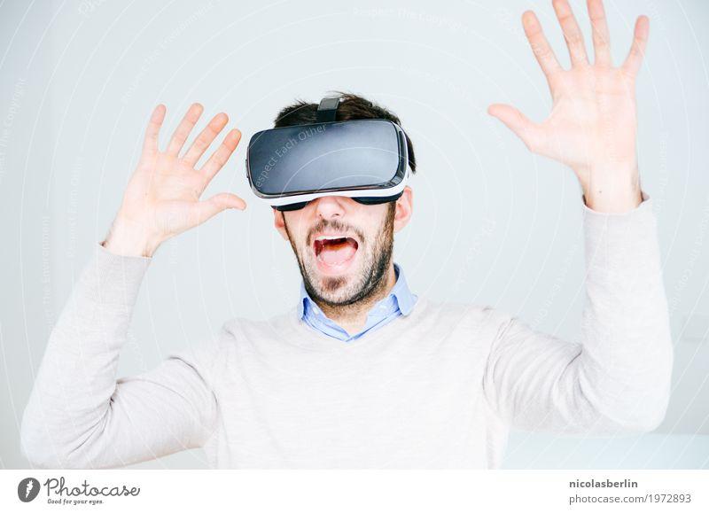 Mann mit VR-Brille erschreckt und hebt die Hände Freude virtuell virtuelle realität Wissenschaften Medienbranche Werbebranche Telekommunikation Computerspiel