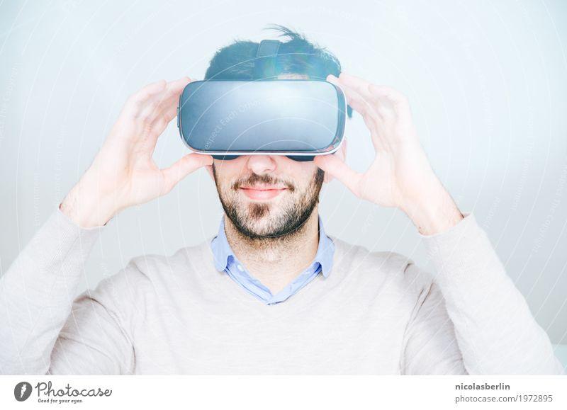 Junger Mann trägt VR-Brille und lächelt auf weißem Hintergrund virtuell Freude Lächeln virtuelle realität virtual reality simulator Spielen Computerspiel Erfolg