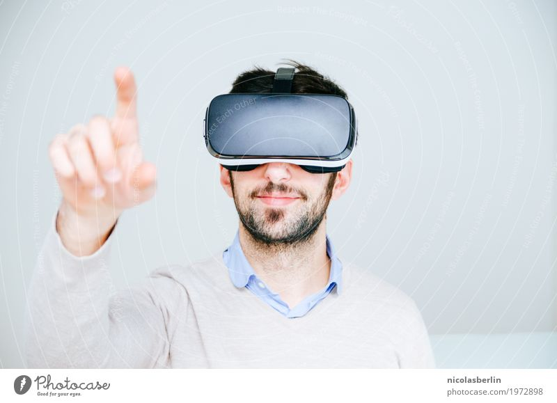 Mittlerer erwachsener Mann, der Virtual-Reality-Simulator Brille trägt, mit dem Finger zeigt und weißer Hintergrund virtuelle Realität VR-Brille
