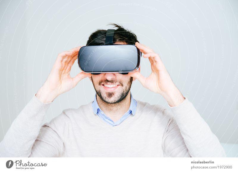 Junger Mann trägt VR Brille und lächelt Design Freude Spielen Expedition Fitness Sport-Training Büro Medienbranche Werbebranche Business Erfolg Sitzung Headset