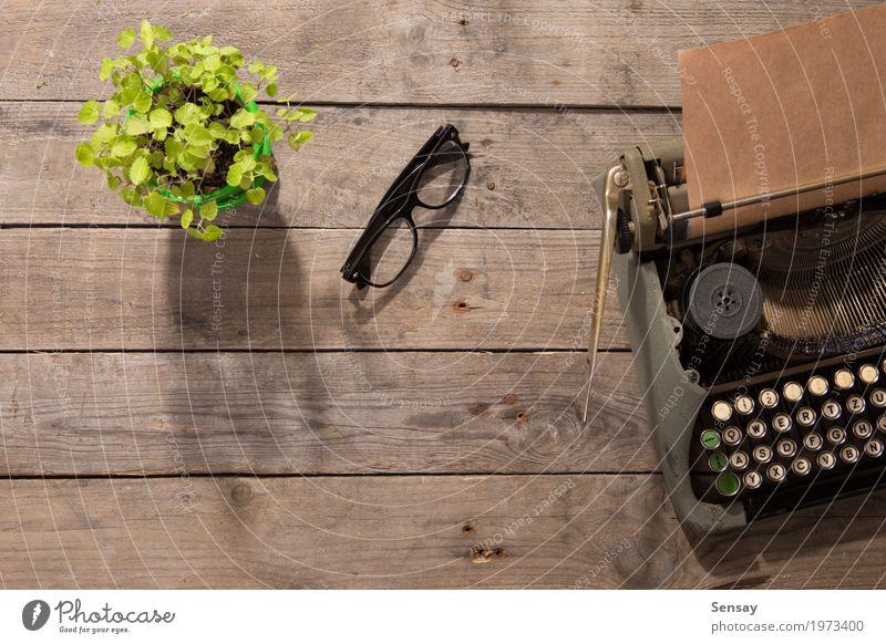 Vintage Schreibmaschine auf dem alten Schreibtisch aus Holz Pflanze grün Textfreiraum Büro retro Tisch Buch Papier schreiben Spuren Zeitung Etage Zeitschrift