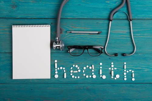Gesundheitskonzept - Pillen, Stethoskop auf dem hölzernen Schreibtisch blau weiß Holz Gesundheitswesen oben Textfreiraum Büro Tisch Papier lesen Medikament