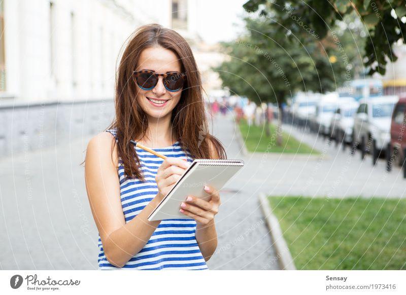 Mädchen mit einem Notizbuch auf der Straße Glück schön Ausflug Sommer Mensch Frau Erwachsene Jugendliche Musiknoten Buch Park Mode Sonnenbrille Papier