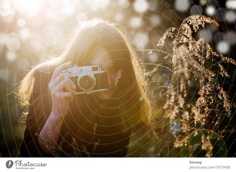 junges Mädchen, das Foto im Park macht Lifestyle Freude schön Haut Gesicht Sommer Fotokamera Mensch Frau Erwachsene Natur Herbst Blume Mode Lächeln Erotik retro