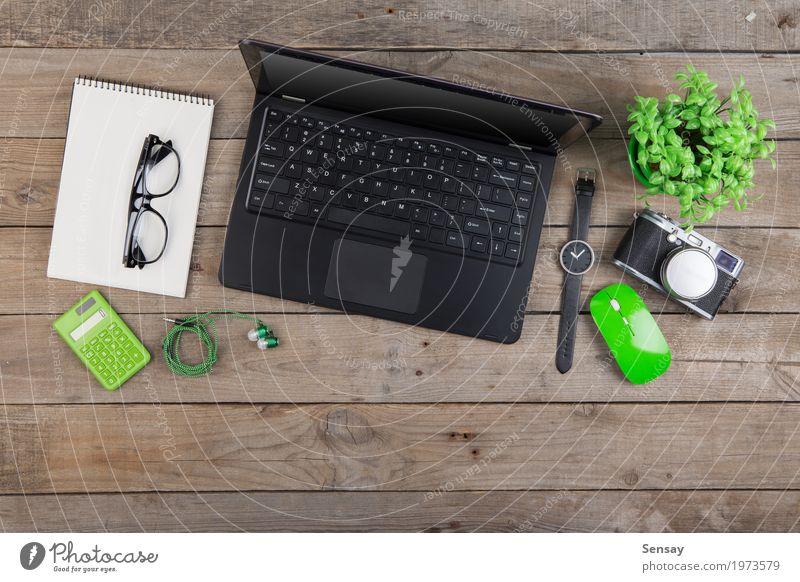 Laptop, Notizblock, Gläser und Kamera auf dem hölzernen Schreibtisch Ferien & Urlaub & Reisen alt Pflanze grün weiß schwarz Holz Business oben Textfreiraum Büro