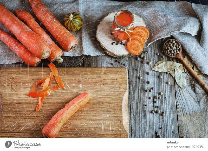 Frische Karotten auf dem Schneidebrett Gemüse Kräuter & Gewürze Ernährung Vegetarische Ernährung Diät Getränk Saft Flasche Glas Löffel Tisch Holz alt frisch