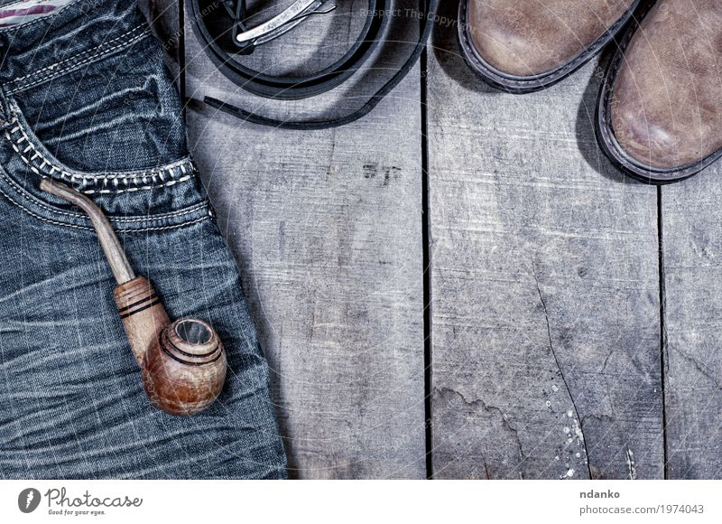 Hölzernes Rohr für das Rauchen auf Blue Jeans Bekleidung Arbeitsbekleidung Hose Jeanshose Leder Schuhe Stiefel alt oben retro blau grau schwarz Röhren Tabak
