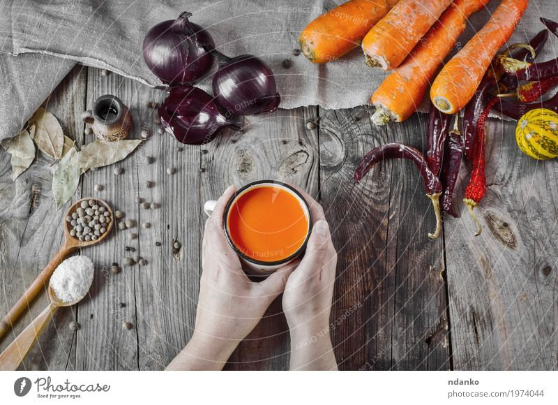 Schale Karottensaft in den weiblichen Händen auf einer grauen Holzoberfläche Gemüse Kräuter & Gewürze Ernährung trinken Erfrischungsgetränk Saft Tasse Löffel