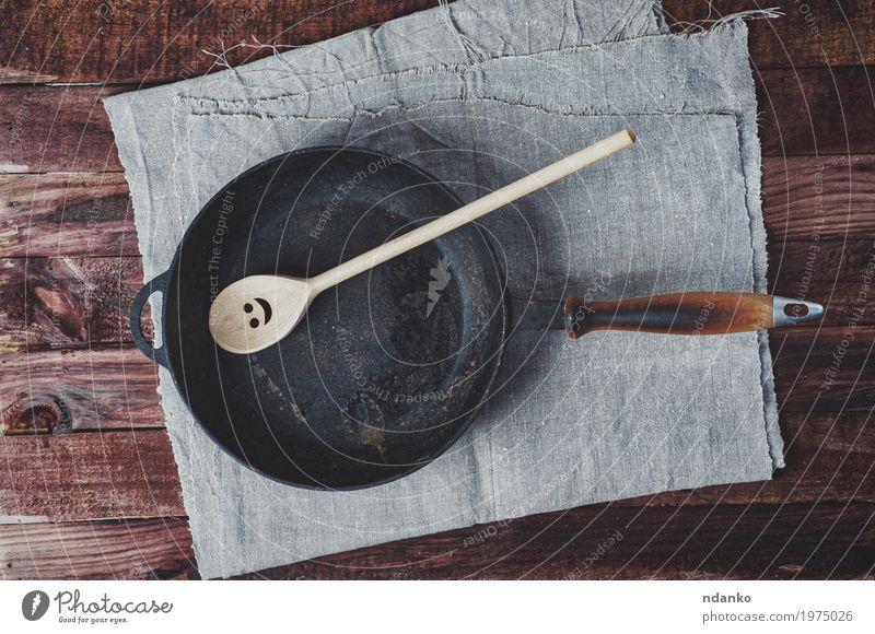 Bratpfannen und ein Holzpaddel Geschirr Pfanne Löffel Tisch Küche Restaurant Werkzeug Stoff Metall oben Sauberkeit braun schwarz Tischwäsche Spachtel Kopie