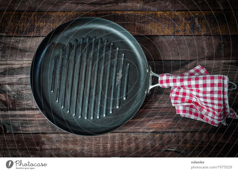 leere Pfanne Grill auf einer Holzoberfläche Geschirr Design Tisch Küche Koch Stoff Metall oben Sauberkeit braun schwarz Tischwäsche Aussicht bügeln braten