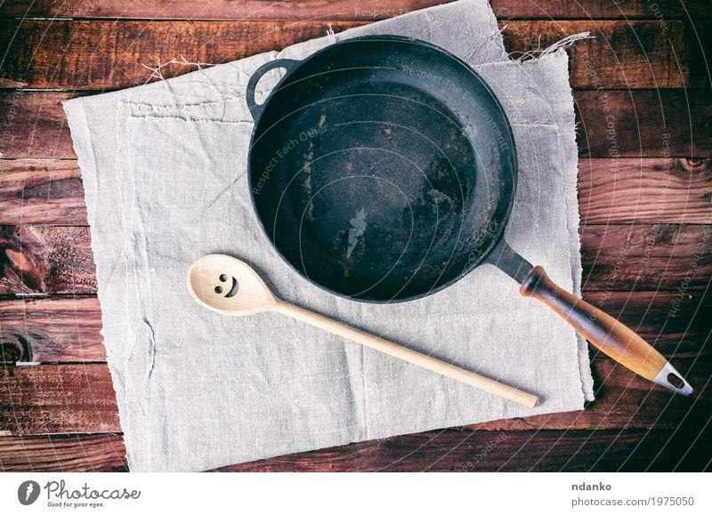 Gusseisenpfanne mit einem Spachtel auf einer grauen Textilserviette Geschirr Pfanne Löffel Design Tisch Küche Restaurant Werkzeug Stoff Holz Metall oben