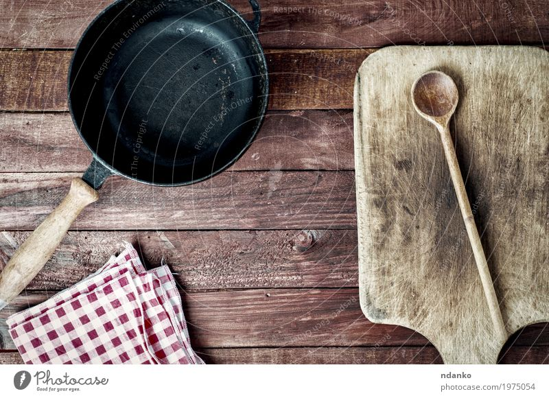 leere schwarze Metallwanne und Schneidebrett auf einer Holzoberfläche Pfanne Löffel Design Tisch Küche Werkzeug Stoff oben Sauberkeit braun Geschirr Tischwäsche