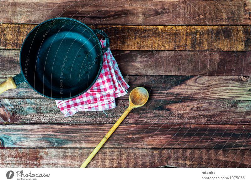 leere schwarze Metallwanne mit einem hölzernen Löffel Geschirr Pfanne Design Tisch Küche Restaurant Stoff Holz oben Sauberkeit braun Tischwäsche Spachtel bügeln