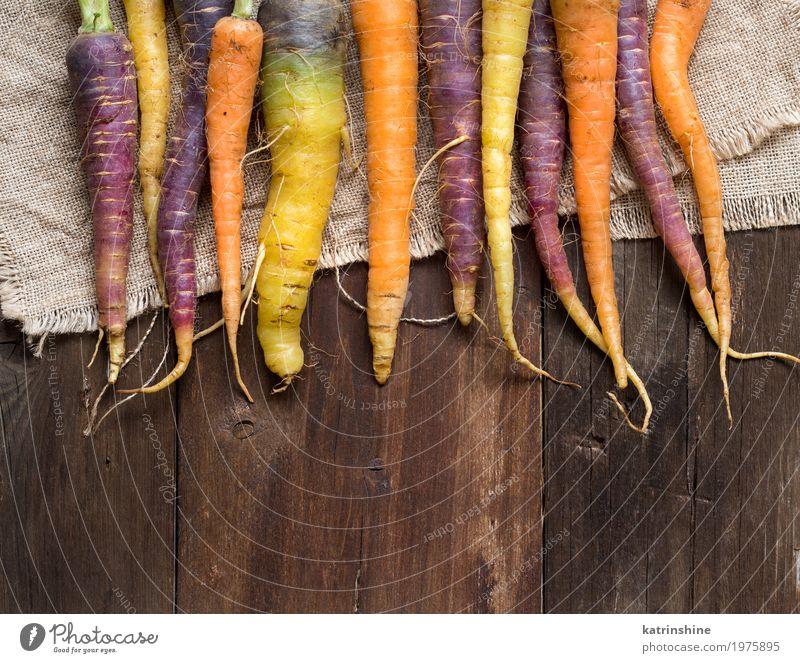 Frische organische Regenbogenkarotten auf einem Holztisch Gemüse Ernährung Vegetarische Ernährung frisch braun gelb Möhre Landwirt Lebensmittel Ernte Gesundheit