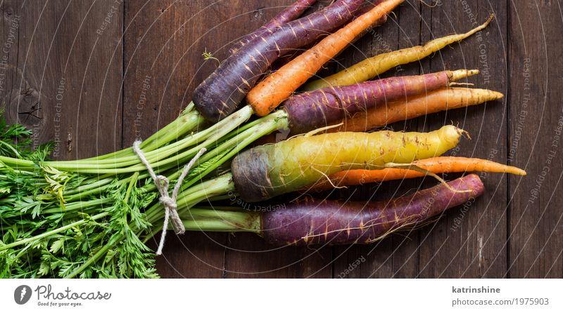 Frische organische Regenbogenkarotten auf einem Holztisch Gemüse Ernährung Vegetarische Ernährung Diät frisch braun gelb Möhre Landwirt Lebensmittel Ernte