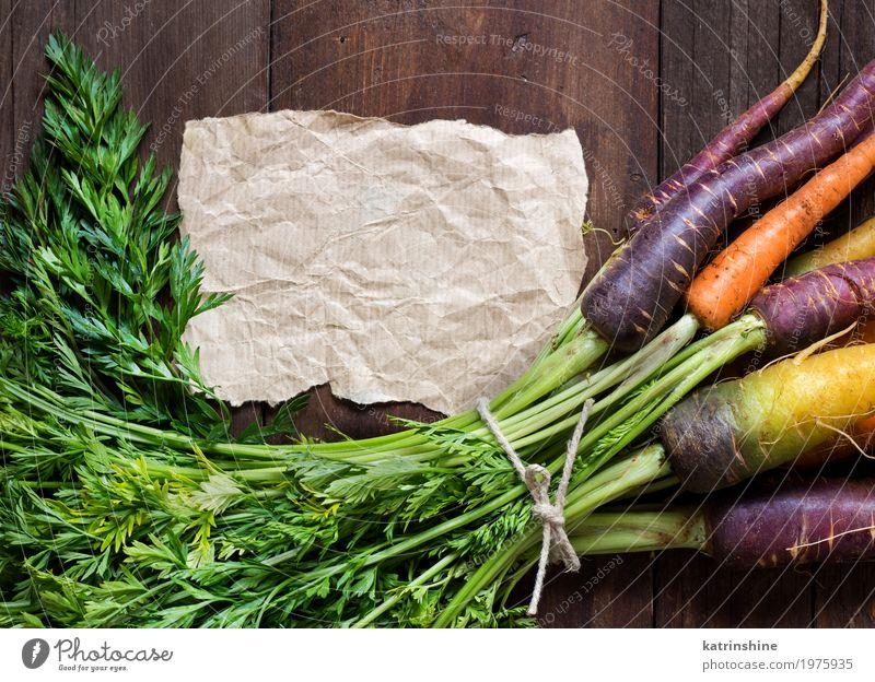 Frische organische Regenbogenkarotten und Kraftpapier auf Holz Gemüse Ernährung Vegetarische Ernährung Papier schreiben frisch braun gelb Möhre Landwirt