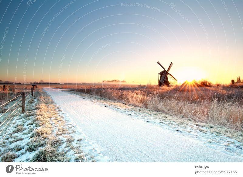 Schnee auf Radweg und Sonne hinter Windmühle Winter Natur Landschaft Himmel Horizont Sonnenaufgang Sonnenuntergang Sonnenlicht Nebel Wiese Straße Wege & Pfade