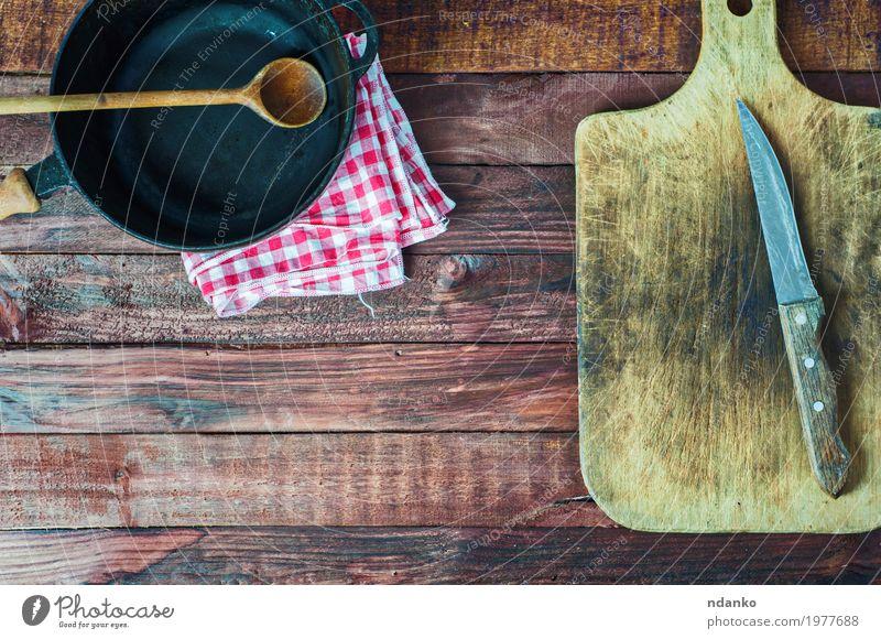 schwarze Gusseisenwanne und Schneidebrett auf brauner Holzoberfläche Geschirr Pfanne Messer Löffel Tisch Küche Restaurant Werkzeug Stoff Metall Stahl alt oben