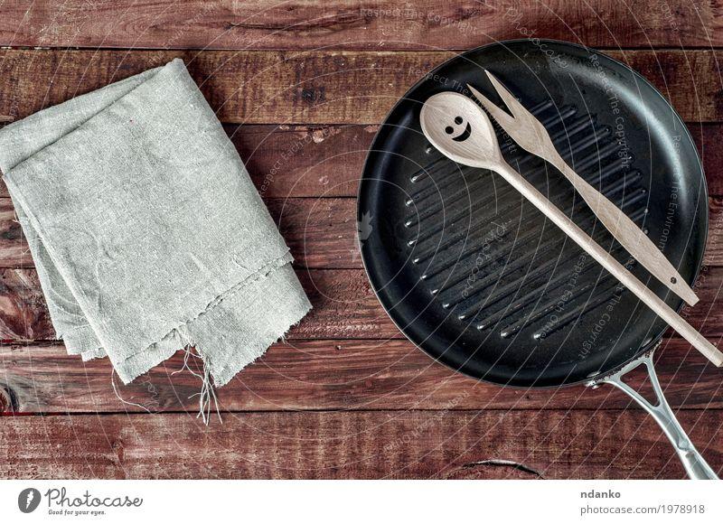 Grillpfanne und hölzernes Küchengeschirr auf einer braunen Holzoberfläche Geschirr Pfanne Löffel Tisch Restaurant Werkzeug Stoff Metall Stahl alt oben