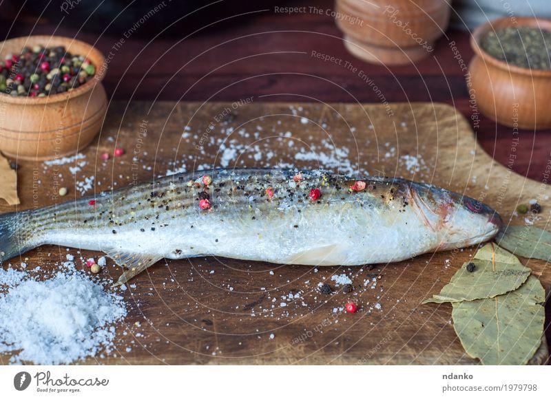 Frischer Stintfisch in den Gewürzen für das Kochen auf einem Küchenbrett Fisch Kräuter & Gewürze Ernährung Essen Diät Tisch Holz frisch oben braun weiß Paprika