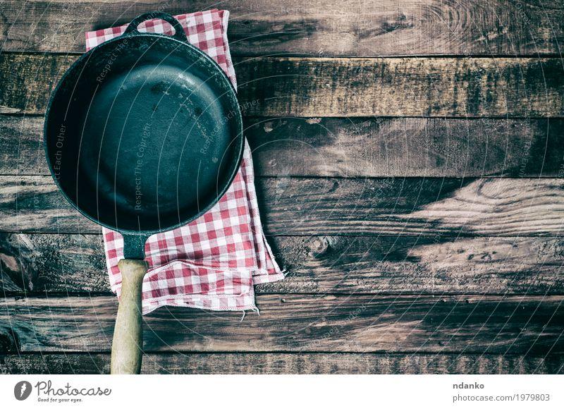 Leere Bratpfanne auf einer Textilserviette schwarz Speise Holz braun oben Metall Aussicht Tisch Sauberkeit Küche Stoff Restaurant Geschirr Top Haushalt