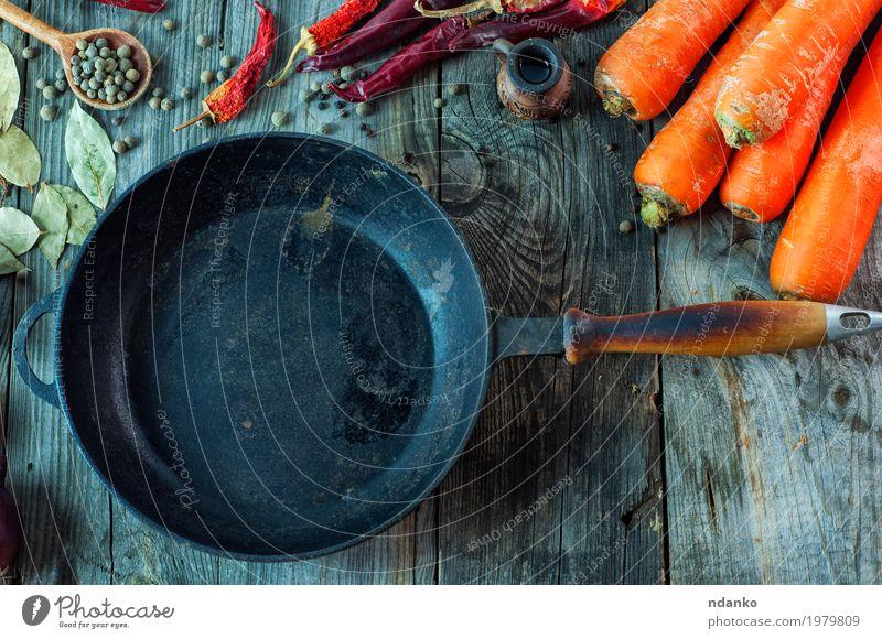 Schwarze leere Gusseisenbratpfanne unter Gemüse Lebensmittel Kräuter & Gewürze Ernährung Vegetarische Ernährung Pfanne Löffel Tisch Küche Holz Metall Essen