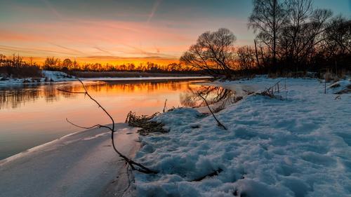 Abend Winterlandschaft. Sonnenuntergang über dem Fluss. Februar Tauwetter Himmel Natur schön Wasser Baum Landschaft rot Umwelt Küste Schnee See braun orange