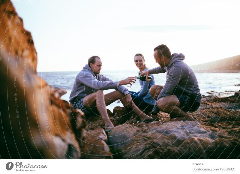 Junge erwachsene Freunde, die Picknick mit Wein durch Ozean haben Mensch Ferien & Urlaub & Reisen Jugendliche Meer Strand 18-30 Jahre Erwachsene Lifestyle