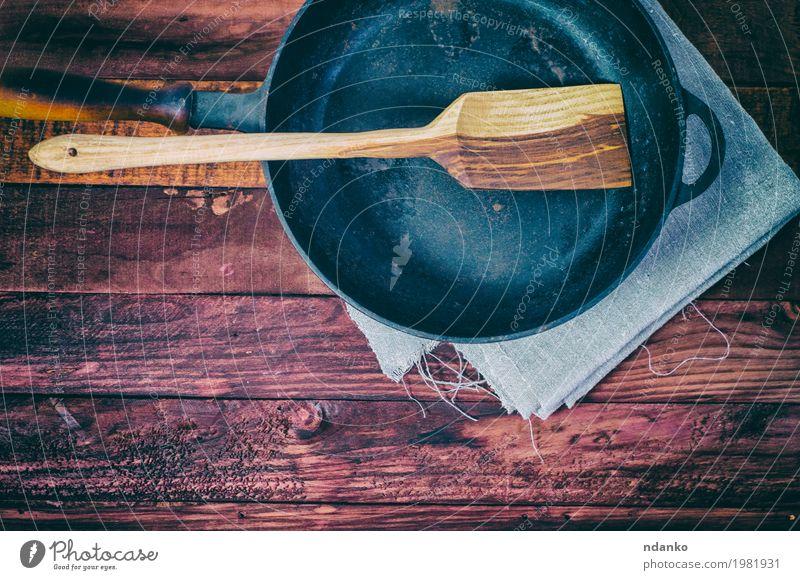 Leere Bratpfanne auf einer braunen Holzoberfläche schwarz Speise oben Metall Aussicht Tisch Sauberkeit Küche Stoff Geschirr Top Werkzeug Haushalt Tischwäsche